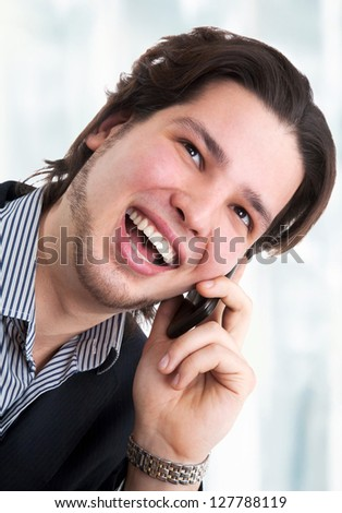 Portrait of happy confident businessman talking by phone in office