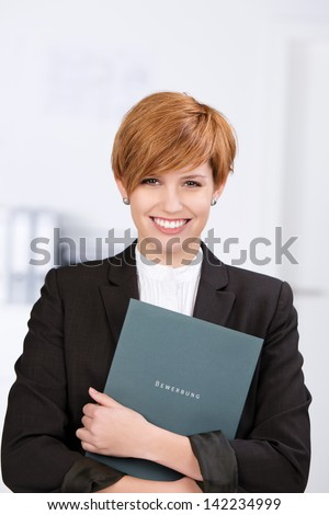 Portrait of happy confident businesswoman holding application book in office - stock photo