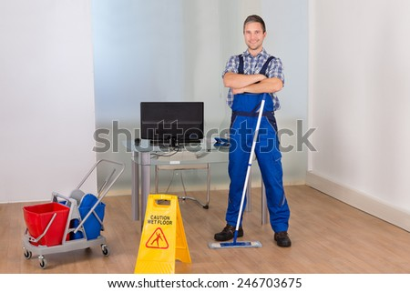 Portrait Of Happy Confident Male Janitor With Cleaning Equipments And Wet Floor Sign In Office - stock photo