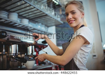 Portrait of happy confident waitress using coffee maker at cafeteria - stock photo