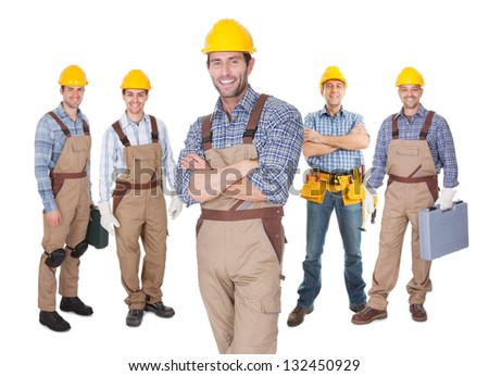 Portrait of happy construction worker standing in front of his team. Isolated on white