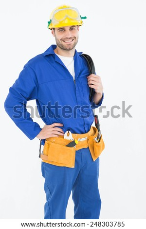 Portrait of happy construction worker standing with hand on hip against white background - stock photo