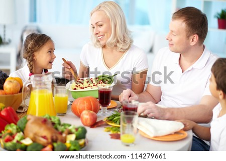 Portrait of happy couple and their children sitting at festive table and going to eat mashed potatoes - stock photo