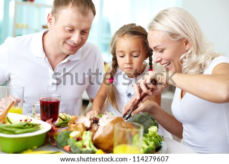 Portrait of happy couple and their daughter sitting at festive table and going to eat roasted turkey