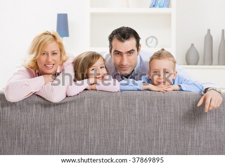 Portrait of happy couple and their two children at home, smiling. - stock photo