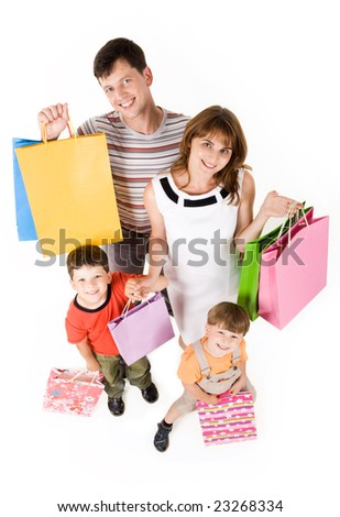 Portrait of happy couple and their two sons with shopping bags looking at camera and smiling - stock photo
