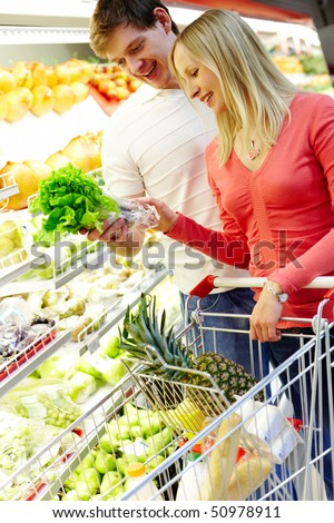 Portrait of happy couple choosing greenery in supermarket - stock photo