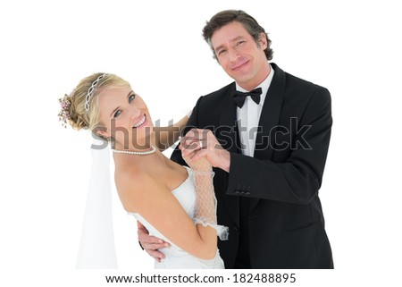 Portrait of happy couple dancing over white background