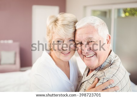 Portrait of happy couple embracing in bedroom at home - stock photo
