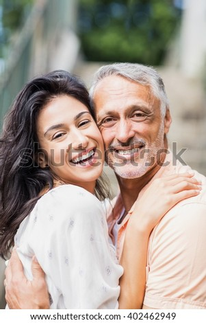 Portrait of happy couple embracing outdoors - stock photo