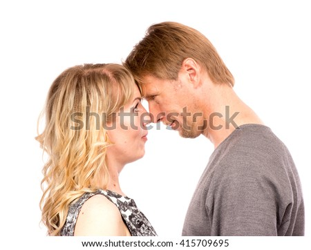 Portrait of happy couple face to face isolated on white background. Attractive man and woman being playful. - stock photo