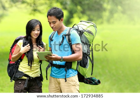 Portrait of happy couple going on a hike together looking at tablet pc in the countryside - stock photo