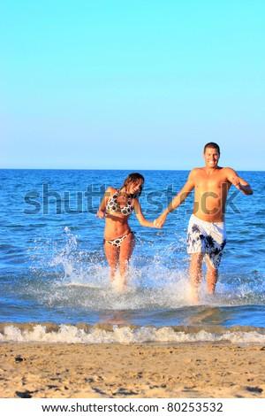 Portrait of happy couple having good time on the beach - stock photo