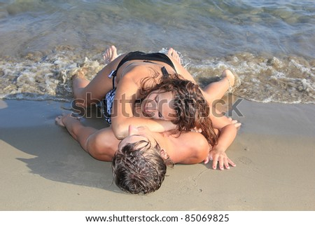 Portrait of happy couple having good time on the beach - stock photo