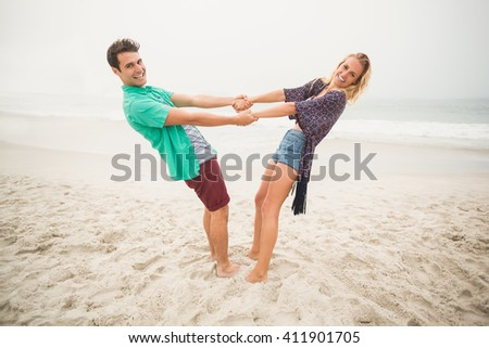 Portrait of happy couple holding hands and bending backwards on the beach - stock photo