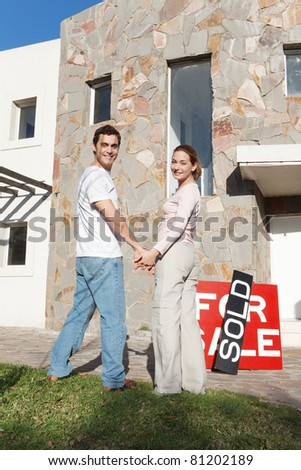 Portrait of happy couple holding hands with new house in background