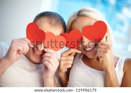 Portrait of happy couple holding red paper hearts by their eyes - stock photo