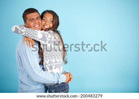 Portrait of happy couple in fashionable pullovers embracing and looking at camera  - stock photo