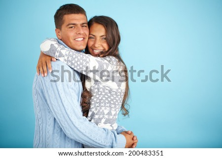 Portrait of happy couple in fashionable pullovers embracing and looking at camera
