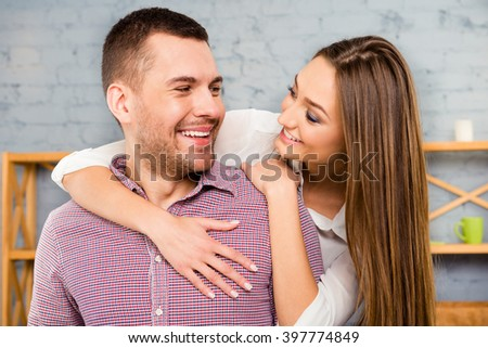 Portrait of happy couple in love embracing and looking at each other - stock photo
