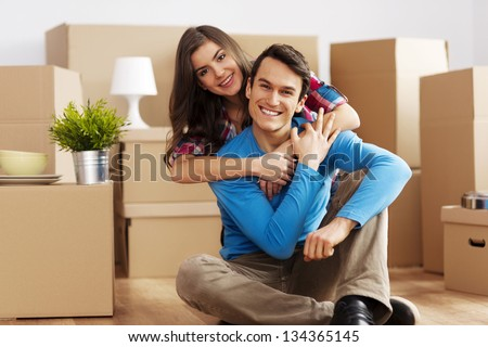 Portrait of happy couple in new home - stock photo
