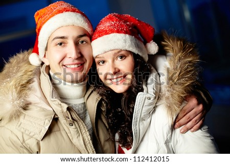 Portrait of happy couple in Santa caps looking at camera with smiles - stock photo