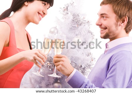 Portrait of happy couple in Santa caps looking at each other while toasting