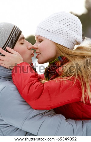 Portrait of happy couple kissing outdoors in winter - stock photo