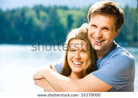 Portrait of happy couple looking at camera while smiling man embracing pretty woman - stock photo