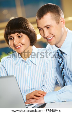 Portrait of happy couple looking at the laptop