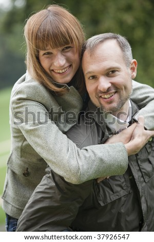 portrait of happy couple, man carrying woman on his back