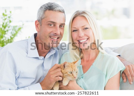 Portrait of happy couple playing with cat in living room - stock photo