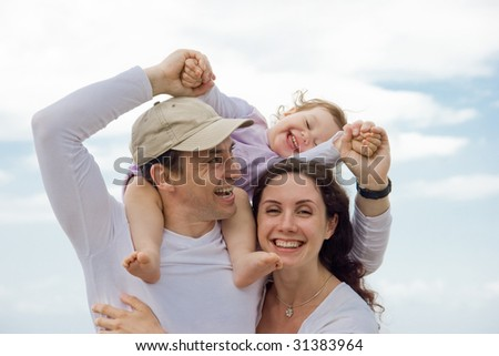 Portrait of happy couple playing with their adorable daughter outdoors and laughing - stock photo