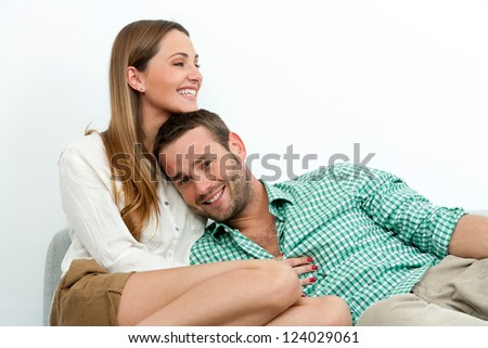 Portrait of happy couple relaxing on couch indoors. - stock photo