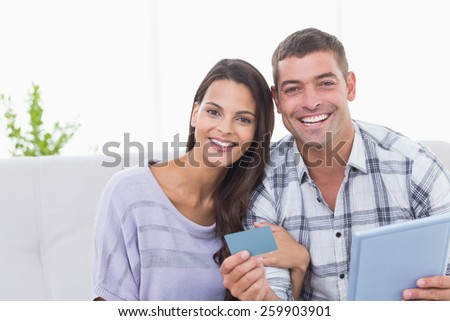 Portrait of happy couple shopping online on digital tablet using credit card at home - stock photo