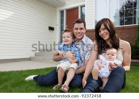 Portrait of happy couple sitting on grass with their children - stock photo
