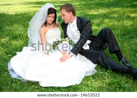 Portrait of happy couple sitting on the grass after marriage