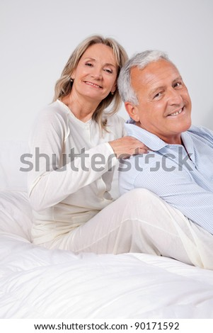 Portrait of happy couple sitting together on bed at home - stock photo