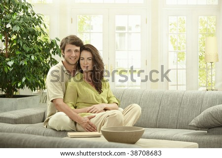 Portrait of happy couple sitting together on couch, embracing. Looking at camera smiling. - stock photo