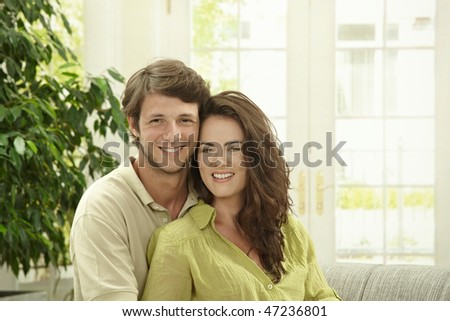 Portrait of happy couple sitting together on sofa embracing. Looking at camera smiling.