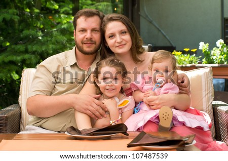 Portrait of happy couple smiling with cute children - stock photo