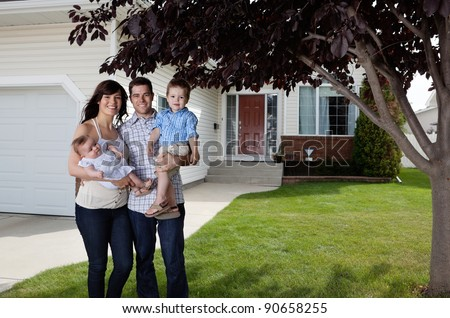 Portrait of happy couple standing with their children in front of house - stock photo
