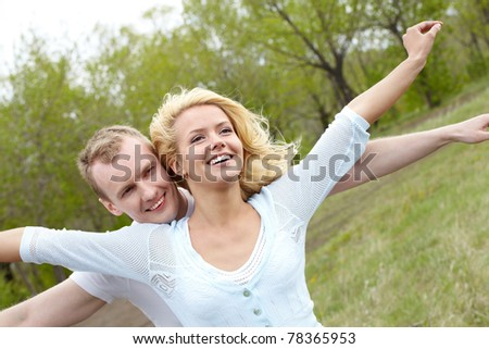 Portrait of happy couple stretching arms in natural environment