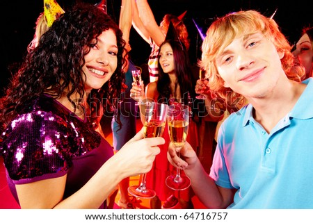 Portrait of happy couple toasting at party on background of joyful friends having fun
