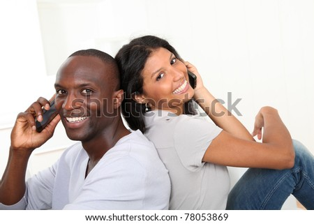 Portrait of happy couple using cellphone - stock photo