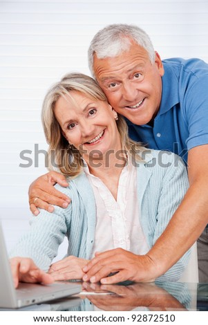 Portrait of happy couple using laptop together at home - stock photo