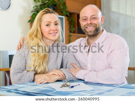 Portrait of happy couple with contract for buying apartment and keys - stock photo