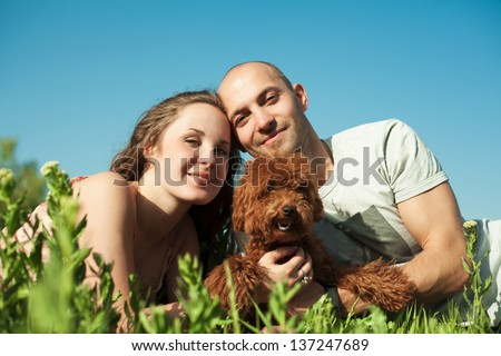 portrait of happy couple with dog lying on the grass