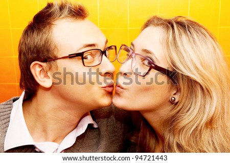 Portrait of happy couple with glasses making kiss in cafe - stock photo