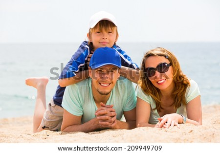 Portrait of happy couple with son at sandy beach - stock photo